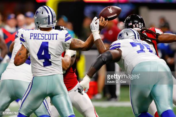 Adrian Clayborn of the Atlanta Falcons strips the ball from Dak Prescott of the Dallas Cowboys during the second half at MercedesBenz Stadium on...