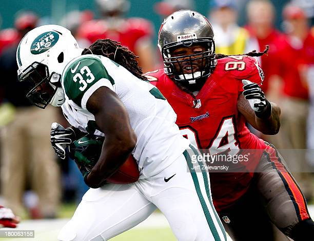 Adrian Clayborn of the Tampa Bay Buccaneers closes in on Robert Malone of the New York Jets during their game at MetLife Stadium on September 8 2013...