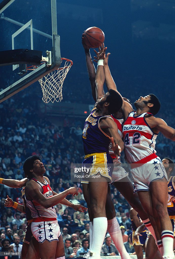 Adrian Dantley of the Los Angeles Lakers battles for a rebound with Elvin Hayes and Greg Ballard of the Washington Bullets during an NBA basketball...