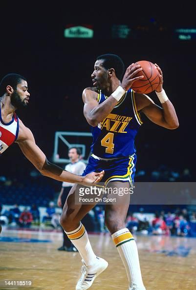 Adrian Dantley of the Utah Jazz pulls the ball back away from Greg Ballard of the Washington Bullets during an NBA basketball game circa 1984 at the...