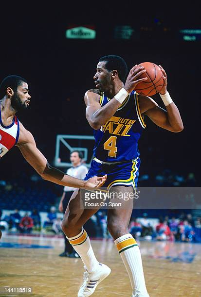 Adrian Dantley of the Utah Jazz pulls the ball back away from Greg Ballard of the Washington Bullets during an NBA basketball game circa 1984 at the...