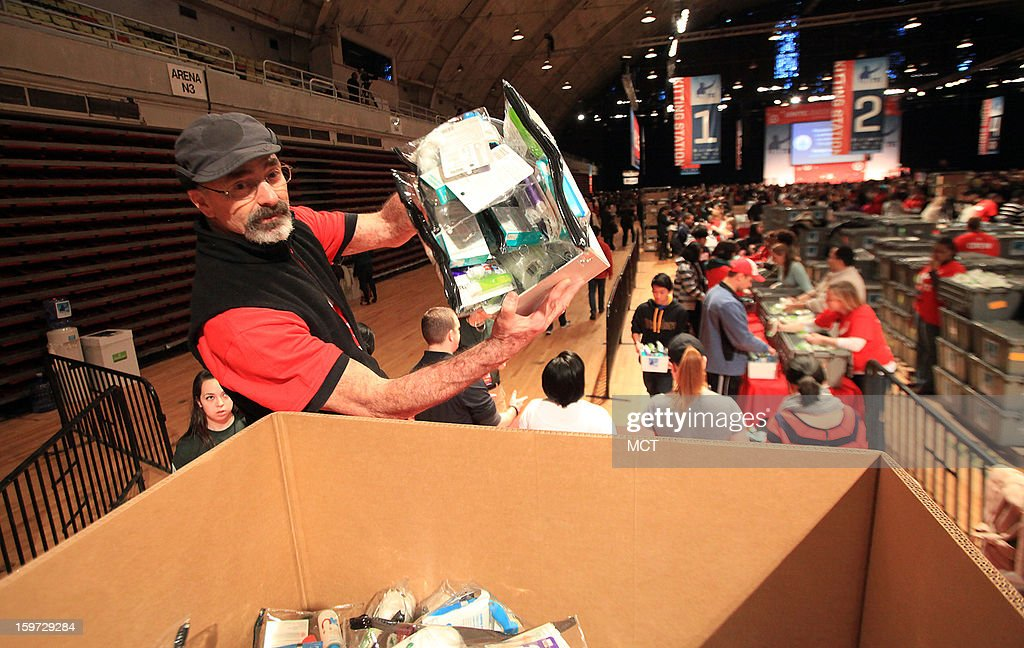 Adrian Engel, of Santa Fe, New Mexico, dumps care kits into a packing box as volunteers continue to assemble the kits during the MLK National Day of Service at the Washington Armory in Washington, D.C, Saturday, January 19, 2013. Thousands of volunteers danced and assembled nearly 100,000 care kits filled with necessities for deployed U.S. service members, Wounded Warriors, veterans and first responders. The service project was part of the 57th Presidential Inauguration.