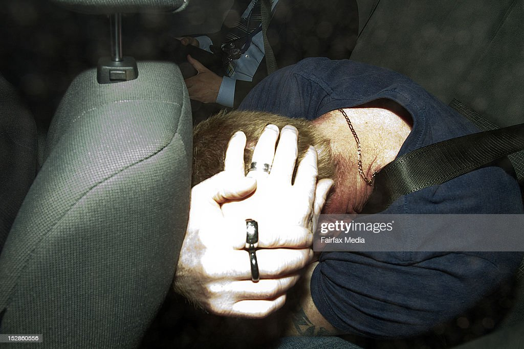 Adrian Ernest Bayley is seen covering his face in a police car after being charged with the rape and murder of Jill Meagher, on September 28, 2012 in Melbourne, Australia. Coburg man Adrian Ernest Bayley was charged overnight with the murder and rape of Irish national Jill Meagher. Her body was found by police buried in a shallow grave north-west of Melbourne. Bayley will appear at a hearing this morning in the Melbourne Magistrates Court. (Photo by Luis Enrique Ascui/The Age/Fairfax Media via Getty Images).