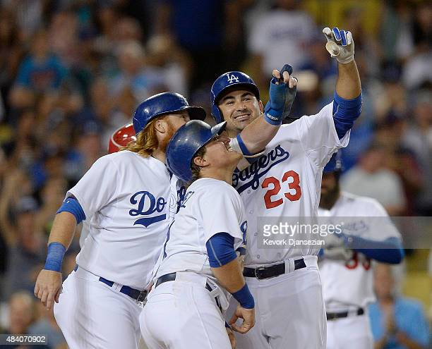 Adrian Gonzalez Enrique Hernandez and Justin Turner of the Los Angeles Dodgers pretend to take a selfie at home plate as they celebrate Gonzalez's...