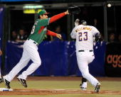 Adrian Gonzalez of Mexico stretches but is unable to catch this errant throw from shorstop Oscar Robles as Brett Willemburg of South Africa reaches...