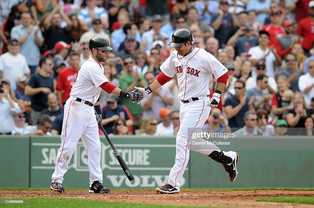 Adrian Gonzalez #28 (R) of the Boston Red Sox gets congratulated by teammate <a gi-track='captionPersonalityLinkClicked' href=/galleries/search?phrase=Dustin+Pedroia&family=editorial&specificpeople=836339 ng-click='$event.stopPropagation()'>Dustin Pedroia</a> #15 after hitting a sixth-inning solo home run against the Toronto Blue Jays at Fenway Park on September 14, 2011 in Boston, Massachusetts.