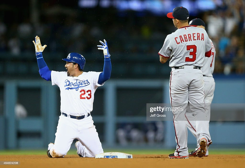 Adrian Gonzalez #23 of the Los Angeles Dodgers celebrates at second base after hitting a single that scored two runs, as <a gi-track='captionPersonalityLinkClicked' href=/galleries/search?phrase=Asdrubal+Cabrera&family=editorial&specificpeople=834042 ng-click='$event.stopPropagation()'>Asdrubal Cabrera</a> #3 of the Washington Nationals looks on in the fifth inning at Dodger Stadium on September 2, 2014 in Los Angeles, California.