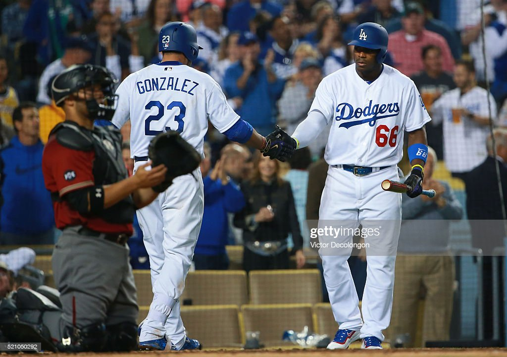 Adrian Gonzalez of the Los Angeles Dodgers celebrates his solo homerun in the fourth inning with Yasiel Puig as catcher Welington Castillo of the...