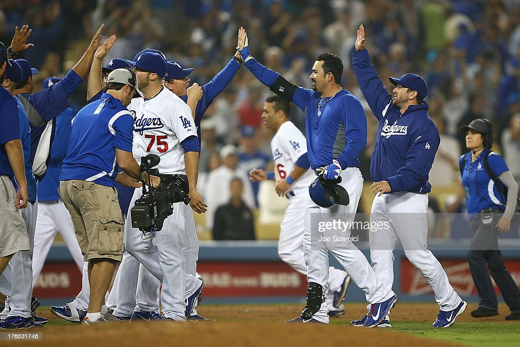 Adrian Gonzalez #23 of the Los Angeles Dodgers celebrates with his team after hitting a game winning double in the twelfth inning against the New York Mets at Dodger Stadium on August 14, 2013 in Los Angeles, California.