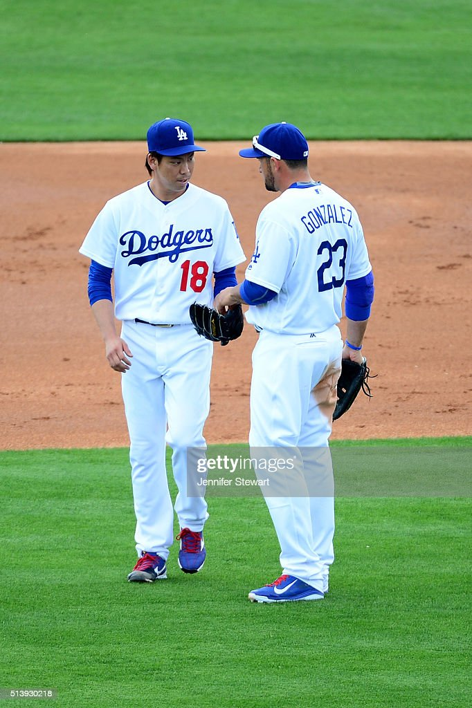 Adrian Gonzalez of the Los Angeles Dodgers hands the baseball to starting pitcher Kenta Maeda during the spring training game at Camelback Ranch on...