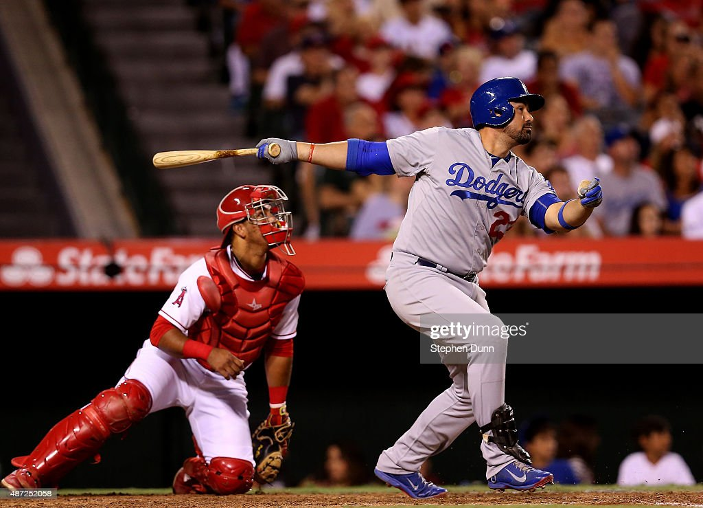Adrian Gonzalez of the Los Angeles Dodgers hits a sacrifice fly score Scott Van Slyke in the sizth inning as catcher Carlos Perez of the Los Angeles...