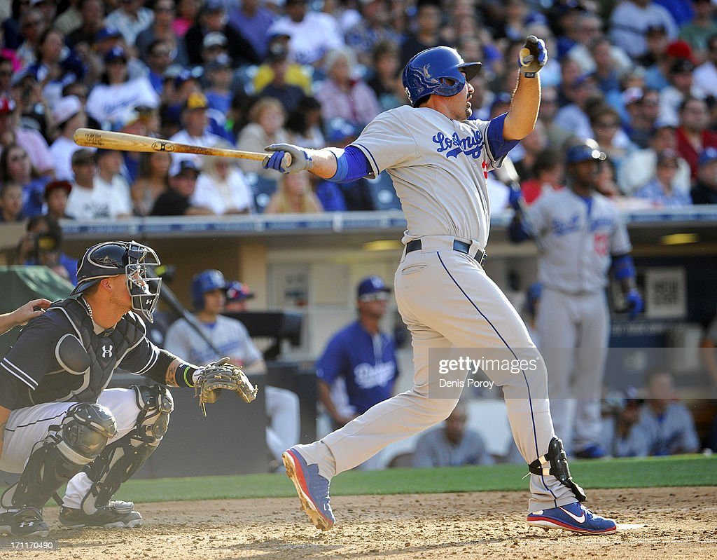 Adrian Gonzalez #23 of the Los Angeles Dodgers hits a solo home run as <a gi-track='captionPersonalityLinkClicked' href=/galleries/search?phrase=Yasmani+Grandal&family=editorial&specificpeople=7510522 ng-click='$event.stopPropagation()'>Yasmani Grandal</a> #12 of the San Diego Padres looks on during the sixth inning of a baseball game at Petco Park on June 22, 2013 in San Diego, California.