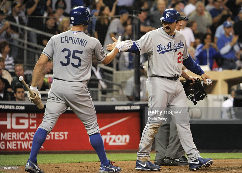 Adrian Gonzalez #23 of the Los Angeles Dodgers is congratulated by <a gi-track='captionPersonalityLinkClicked' href=/galleries/search?phrase=Chris+Capuano&family=editorial&specificpeople=228059 ng-click='$event.stopPropagation()'>Chris Capuano</a> #35 after he scored during the fourth inning of a baseball game against the San Diego Padres at Petco Park on September 27, 2012 in San Diego, California.
