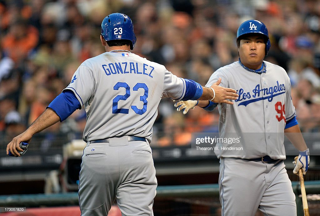 Adrian Gonzalez #23 of the Los Angeles Dodgers is congratulated by pitcher Hyun-Jin Ryu #99 after Gonzalez scored on an RBI single from Mark Ellis #14 in the third inning against the San Francisco Giants at AT&T Park on July 5, 2013 in San Francisco, California.