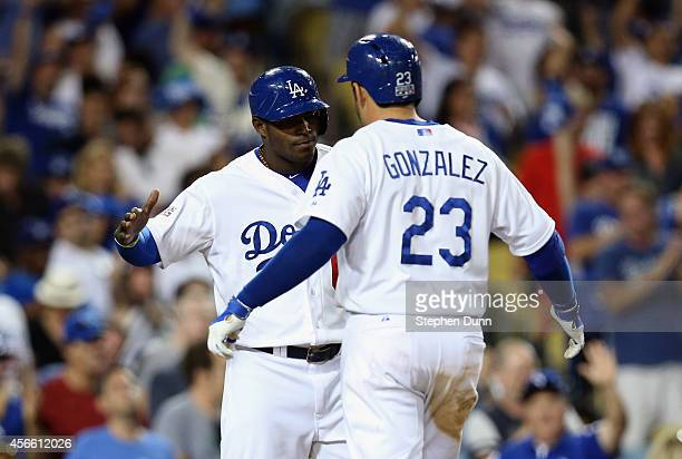 Adrian Gonzalez of the Los Angeles Dodgers is greeted by teammate Yasiel Puig after a two run homerun in the eighth inning of Game One of the...