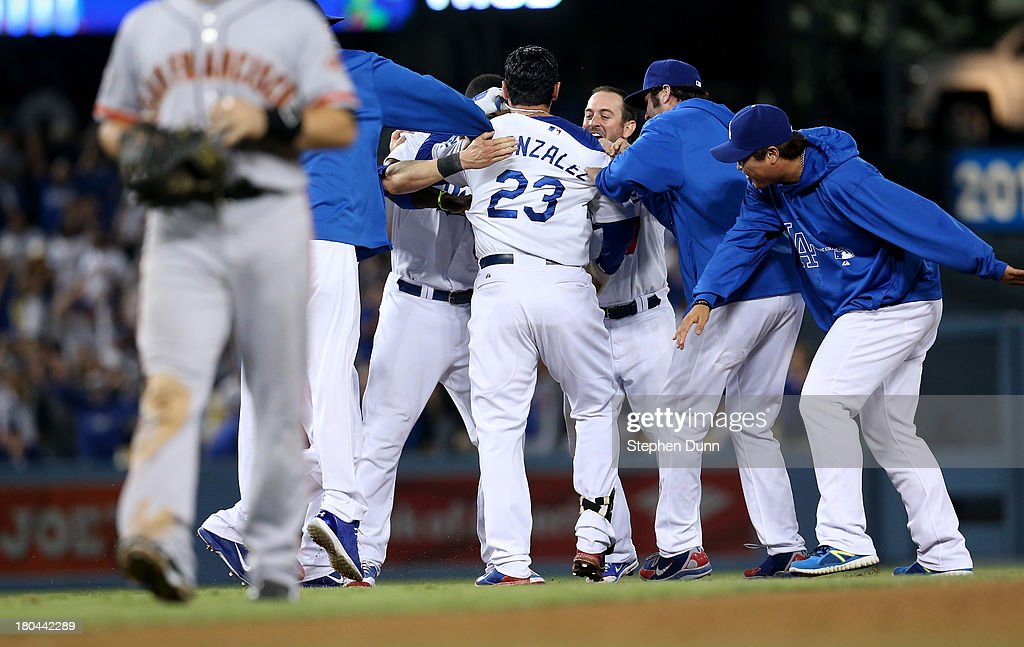 Adrian Gonzalez #23 of the Los Angeles Dodgers is mobbed by teammates after hitting a walk off RBI single in the tenth inning to win the game against the San Francisco Giants at Dodger Stadium on September 12, 2013 in Los Angeles, California. The Dodgers won 3-2 in ten innings.