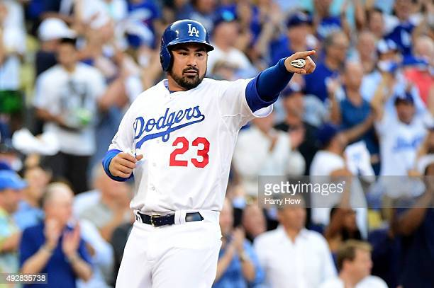 Adrian Gonzalez of the Los Angeles Dodgers points after he scores a run in the first inning against the New York Mets in game five of the National...