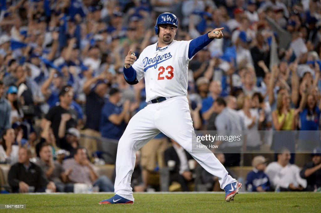 Adrian Gonzalez #23 of the Los Angeles Dodgers points after scoring a run in the fourth inning against the St. Louis Cardinals in Game Four of the National League Championship Series at Dodger Stadium on October 15, 2013 in Los Angeles, California.