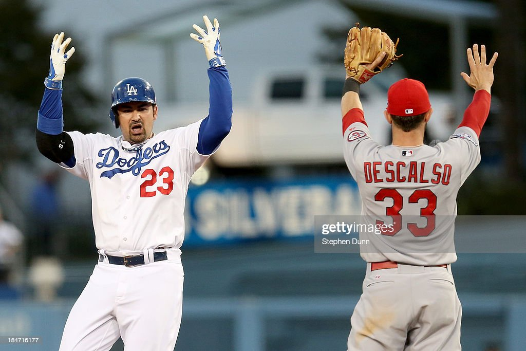 Adrian Gonzalez #23 of the Los Angeles Dodgers reacts after hitting a double in the fourth inning alongside <a gi-track='captionPersonalityLinkClicked' href=/galleries/search?phrase=Daniel+Descalso&family=editorial&specificpeople=6800752 ng-click='$event.stopPropagation()'>Daniel Descalso</a> #33 of the St. Louis Cardinals in Game Four of the National League Championship Series at Dodger Stadium on October 15, 2013 in Los Angeles, California.