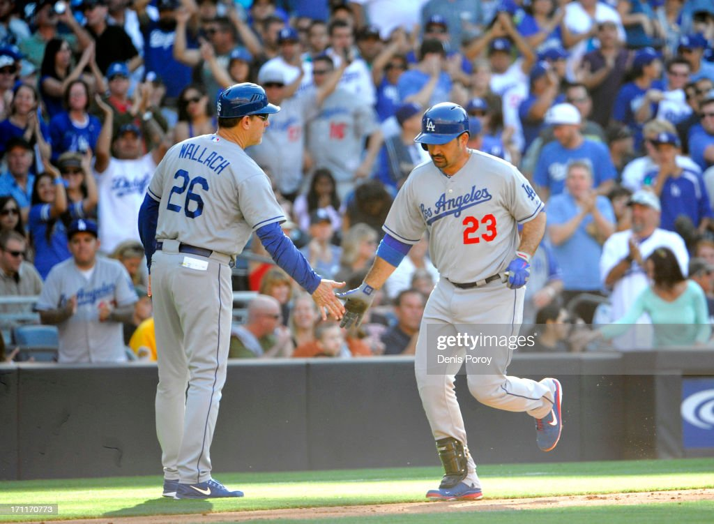 Adrian Gonzalez #23 of the Los Angeles Dodgers, right, is congratulated by Tim Wallach #26 after he hit a solo home run during the sixth inning of a baseball game against the San Diego Padres at Petco Park on June 22, 2013 in San Diego, California.