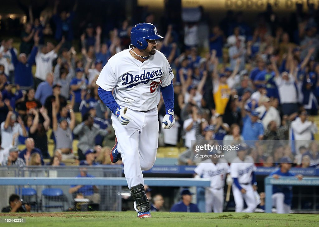 Adrian Gonzalez #23 of the Los Angeles Dodgers runs to first as he watches his walk off RBI single in the tenth inning to win the game against the San Francisco Giants at Dodger Stadium on September 12, 2013 in Los Angeles, California. The Dodgers won 3-2 in ten innings.