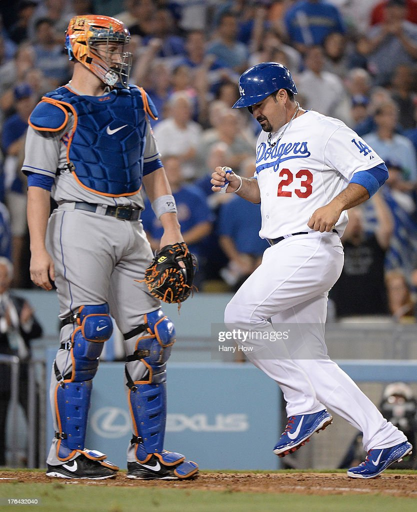 Adrian Gonzalez #23 of the Los Angeles Dodgers scores a run to take the lead off of a Yasiel Puig #66 sacrifice fly in front of <a gi-track='captionPersonalityLinkClicked' href=/galleries/search?phrase=John+Buck&family=editorial&specificpeople=213730 ng-click='$event.stopPropagation()'>John Buck</a> #44 of the New York Mets during the sixth inning at Dodger Stadium on August 12, 2013 in Los Angeles, California.
