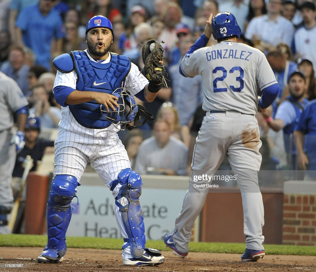 Adrian Gonzalez #23 of the Los Angeles Dodgers scores as catcher <a gi-track='captionPersonalityLinkClicked' href=/galleries/search?phrase=Dioner+Navarro&family=editorial&specificpeople=593062 ng-click='$event.stopPropagation()'>Dioner Navarro</a> #30 of the Chicago Cubs reacts during the third inning on August 1, 2013 at Wrigley Field in Chicago, Illinois.