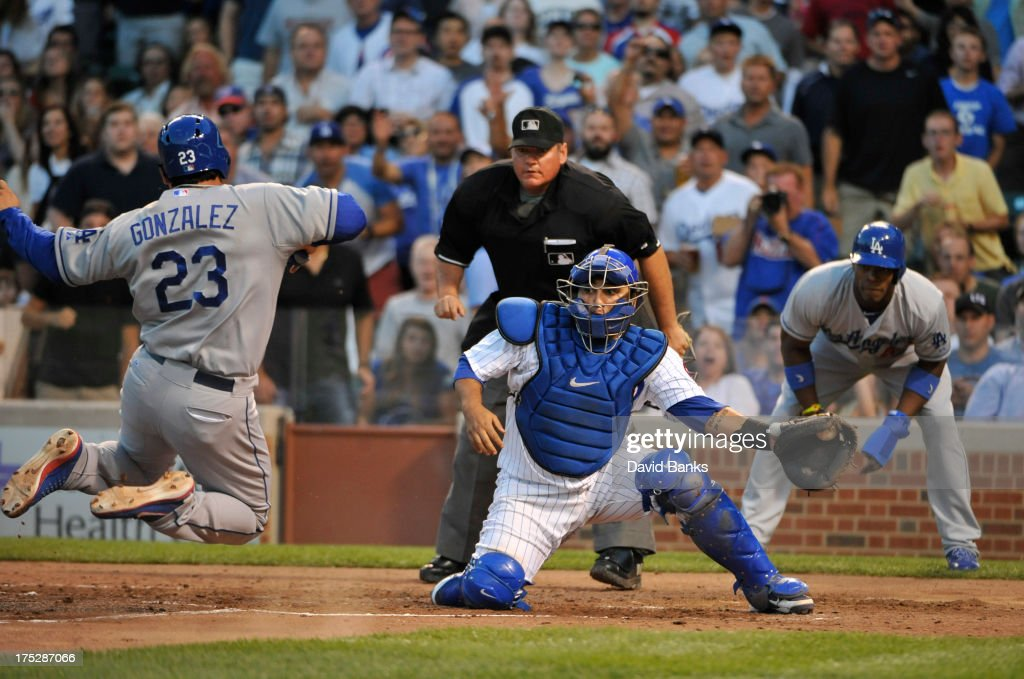 Adrian Gonzalez #23 of the Los Angeles Dodgers scores as <a gi-track='captionPersonalityLinkClicked' href=/galleries/search?phrase=Dioner+Navarro&family=editorial&specificpeople=593062 ng-click='$event.stopPropagation()'>Dioner Navarro</a> #30 of the Chicago Cubs takes the throw during the third inning on August 1, 2013 at Wrigley Field in Chicago, Illinois.