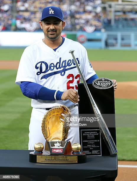 Adrian Gonzalez of the Los Angeles Dodgers stands with his 2014 Silver Slugger and Gold Gove awards after a presentation before the game with the San...