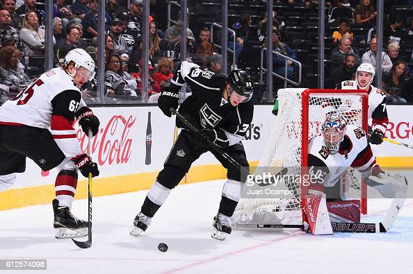 Adrian Kempe of the Los Angeles Kings skates with the puck against Kyle Wood and Justin Peters of the Arizona Coyotes during a preseason game on...