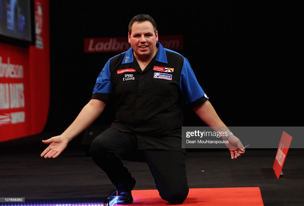 Adrian Lewis of England celebrates on his knee after winning against Gary Anderson of Scotland in the Final of the 2011 Ladbrokescom World Darts...