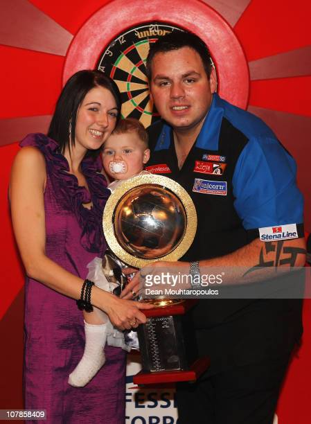 Adrian Lewis of England celebrates with his girlfriend Katie and daughter Myla after winning against Gary Anderson of Scotland in the Final of the...