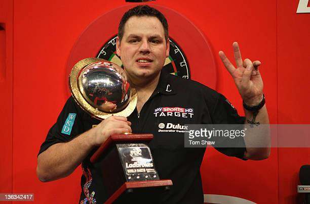 Adrian Lewis of England celebrates with the trophy after winning the final against Andy Hamilton of England during the Final of the World Darts...
