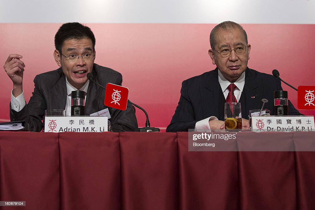 Adrian Li, deputy chief executive officer of Bank of East Asia Ltd. (BEA), left, speaks as David Li, chairman and chief executive officer, looks on during the company's annual results news conference in Hong Kong, China, on Tuesday, Feb. 26, 2013. Bank of East Asia, Hong Kong's largest family-run lender, said 2012 profit jumped 39 percent as trading income climbed, helping offset a decline in profit from the mainland China business. Photographer: Jerome Favre/Bloomberg via Getty Images