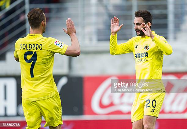 Adrian Lopez of Villarreal CF celebrates with his teammate Roberto Soldado of Villarreal CF after scoring the opening goal during the La Liga match...