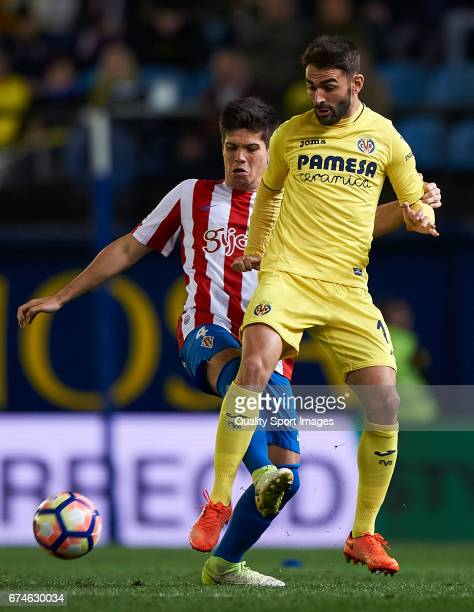 Adrian Lopez of Villarreal competes for the ball with Jorge Mere of Real Sporting de Gijon during the La Liga match between Villarreal CF and Real...