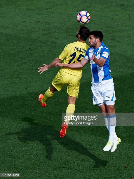 Adrian Lopez of Villarreal competes for the ball with Pablo Insua Blanco of Leganes during the La Liga match between Villarreal CF and CD Leganes at...