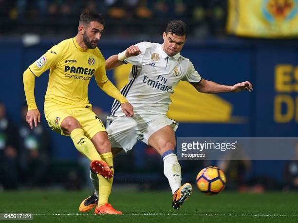 Adrian Lopez of Villarreal competes for the ball with Pepe of Real Madrid during the La Liga match between Villarreal CF and Real Madrid at Estadio...