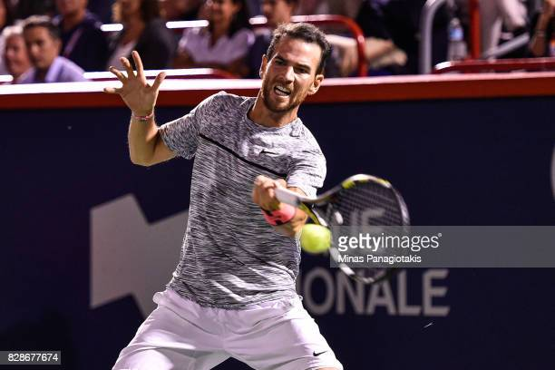 Adrian Mannarino of France hits a return against Milos Raonic of Canada during day six of the Rogers Cup presented by National Bank at Uniprix...