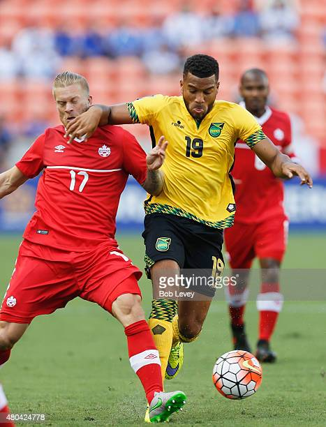 Adrian Mariappa of Jamaica fends off Russell Teibert of Canada as he brings the ball up the field in the first half at BBVA Compass Stadium on July...