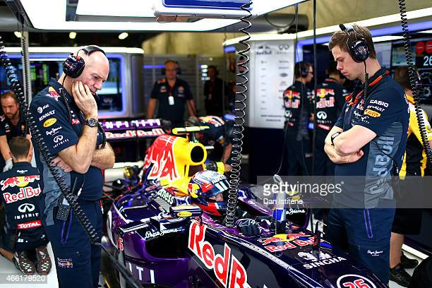 Adrian Newey the Chief Technical Officer of Infiniti Red Bull Racing looks at the car as Daniil Kvyat of Russia and Infiniti Red Bull Racing sits in...