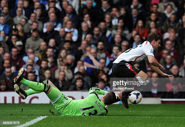 Adrian of West Ham United challenges Jon Flanagan of Liverpool in the box and concedes a penalty during the Barclays Premier League match between...