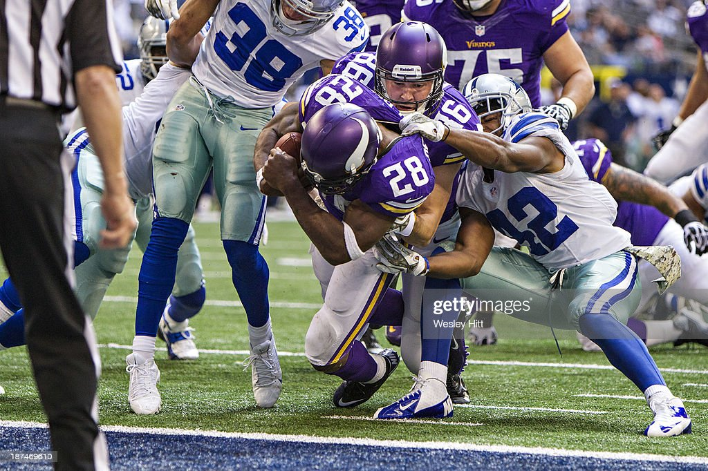 Adrian Peterson #28 is helped into the end zone by Chase Ford #86 of the Minnesota Vikings for a touchdown against the Dallas Cowboys at AT&T Stadium on November 3, 2013 in Arlington, Texas. The Cowboys defeated the Vikings 27-23.