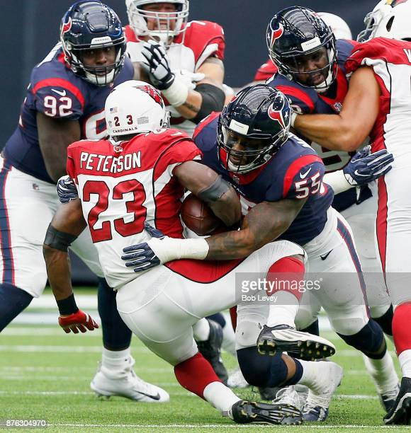 Adrian Peterson of the Arizona Cardinals is hit by Benardrick McKinney of the Houston Texans for a three yard loss in the second quarter at NRG...