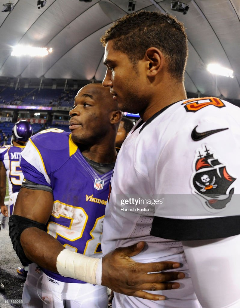 Adrian Peterson #28 of the Minnesota Vikings and Josh Freeman #5 of the Tampa Bay Buccaneers speak after their game on October 25, 2012 at Mall of America Field at the Hubert H. Humphrey Metrodome in Minneapolis, Minnesota. The Buccaneers defeated the Vikings 36-17.