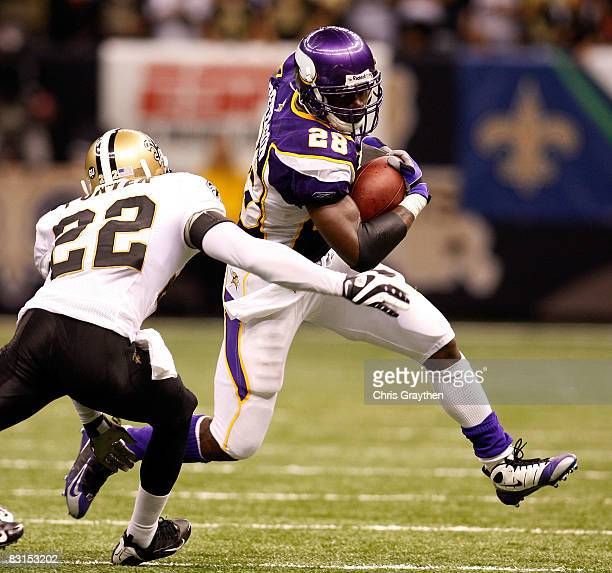 Adrian Peterson of the Minnesota Vikings avoids a tackle by Tracy Porter of the New Orleans Saints on October 6 2008 at the Superdome in New Orleans...