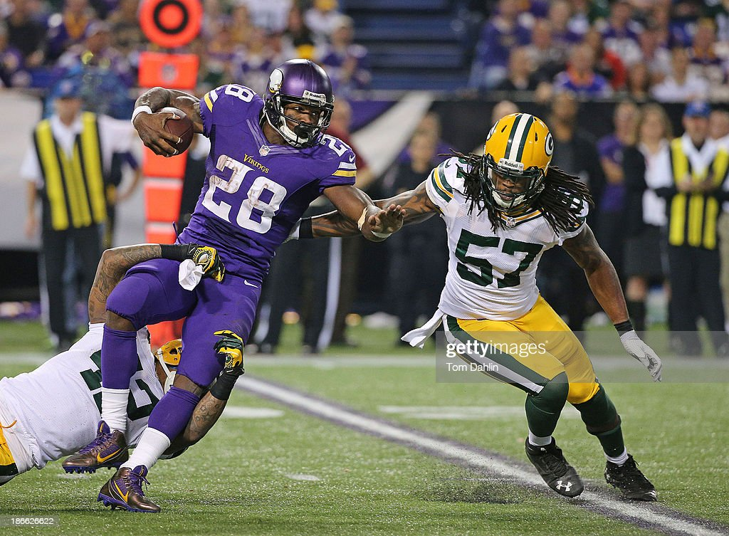 Adrian Peterson #28 of the Minnesota Vikings carries the ball and is tackled by Morgan Burnett #42 and Jamari Lattimore #57 of the Green Bay Packers during an NFL game against the Green Bay Packers at Mall of America Field at the Hubert H. Humphrey Metrodome on October 27, 2013 in Minneapolis, Minnesota.