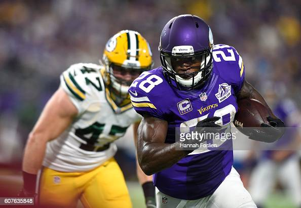 Adrian Peterson of the Minnesota Vikings carries the ball as defender Jake Ryan of the Green Bay Packers pursues him during their game on September...