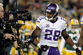 Adrian Peterson of the Minnesota Vikings celebrates scoring a touchdown during the third quarter against the Green Bay Packers at Lambeau Field on...