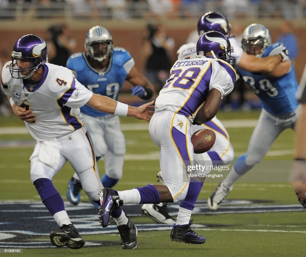 Adrian Peterson of the Minnesota Vikings fumbles a hand off from Brett Favre in the first quarter against the Detroit Lions at Ford Field on...